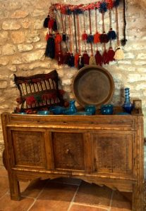 An ornate hand carved wooden sideboard displaying blue bowls and jugs from Pakistan's North-West Frontier